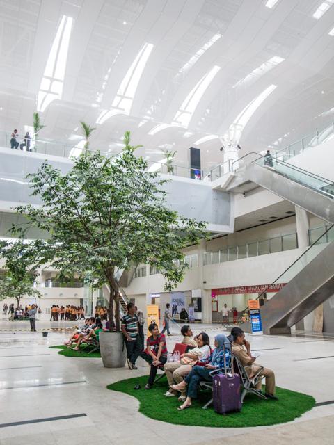 Interior Bandara Kuala Namu yang didominasi oleh warna putih dan kaca memberikan kesan modern.