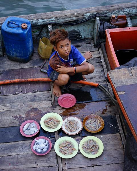 Anak nelayan berusaha menjual udang dan cumi kepada pengunjung pantai Ancol. ISO 400m f/3.5, 1/50 detik, 35mm